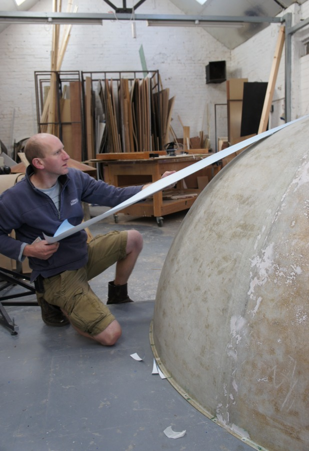 Vinyl map being attached to the largest globe