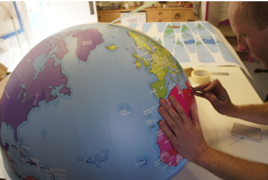 Vinyl map being attached to a large globe